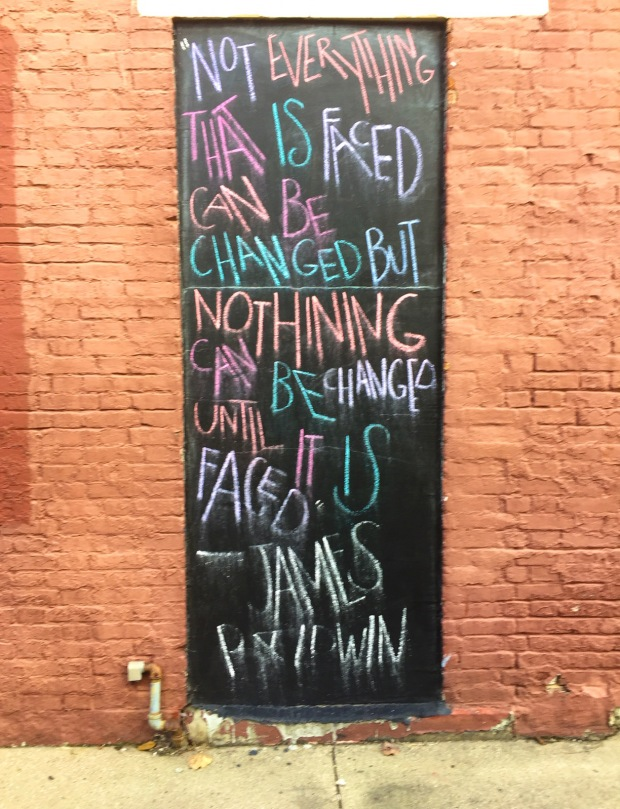 photo of chalked quote by James Baldwin on a panel.